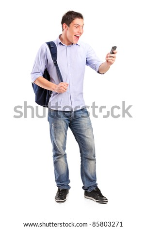 Full length portrait of a smiling young man looking at a cell phone isolated on white background