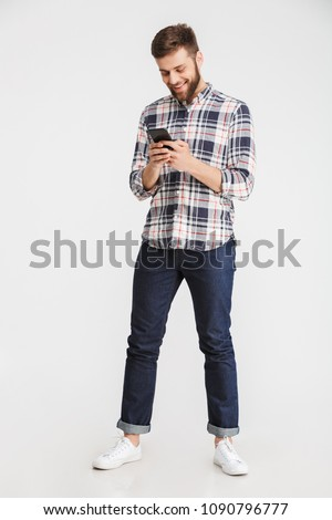Full length portrait of a smiling young man using mobile phone isolated over white background
