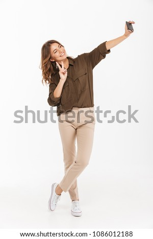 Full length portrait of a smiling young woman taking selfie with mobile phone isolated over white background