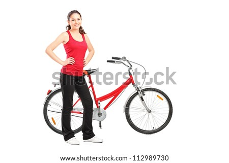 Full length portrait of a sporty girl posing next to a bike isolated on white background
