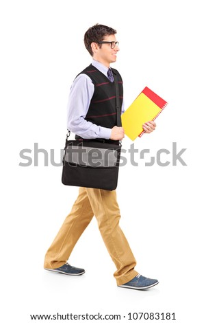 Full length portrait of a student walking with notebooks in his hand isolated on white background
