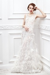 Full length portrait of a stunning young woman in a white luxury dress posing in a white room with classic vintage interior. Fashion shot. Wedding dress.