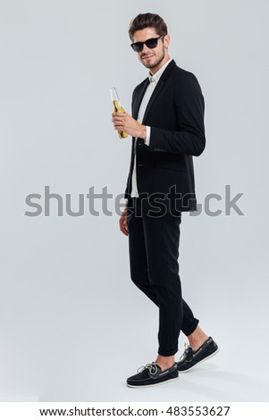 27a187907812 Full length portrait of a stylish young man in black suit and sunglasses  holding beer bottle