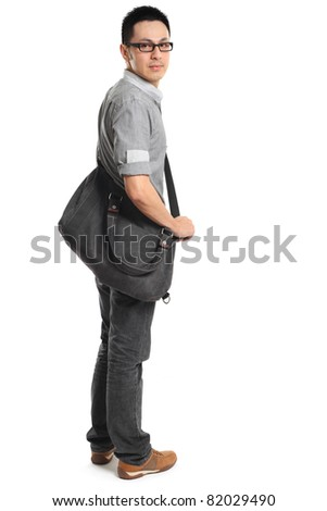 Full length portrait of a stylish young man standing and holding a bag. Isolated on white background.