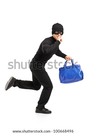 Full length portrait of a thief running with a stolen purse and finger on lips gesturing silence isolated on white background - stock photo