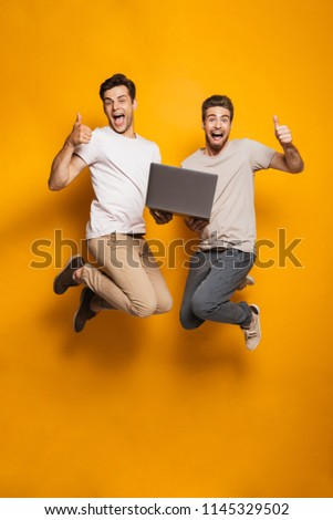 Full length portrait of a two excited young men best friends jumping holding laptop computer and showing thumbs up isolated over yellow background
