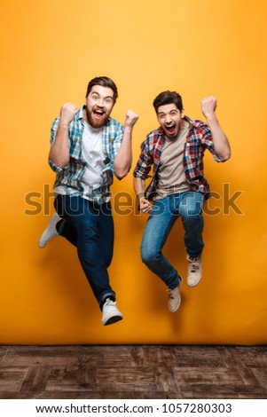 Full length portrait of a two excited young men celebrating while jumping together isolated over yellow background #1057280303