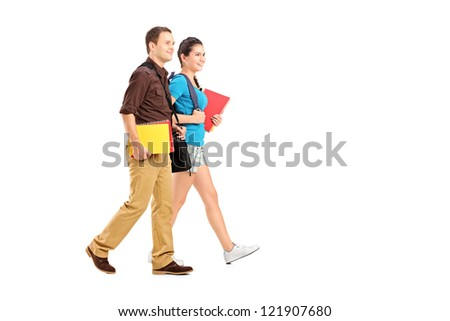 Full length portrait of a two students holding books and walking isolated on white background