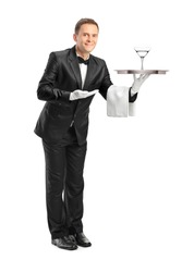 Full length portrait of a waiter holding a tray with a glass of cocktail on it isolated on white background