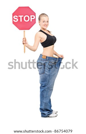 Full length portrait of a weightloss girl holding a traffic sign stop isolated on white background