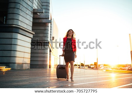 Full length portrait of a well dressed business woman pulling a suitcase at the airport. #705727795