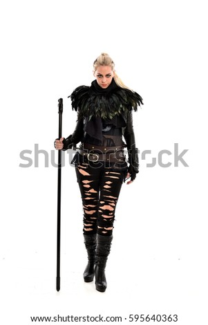 Stock Photo full length portrait of a young blonde lady wearing a futuristic torn leather outfit. isolated against a white background.