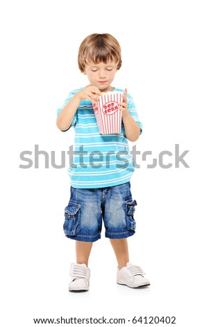 Full length portrait of a young boy eating popcorn isolated against white background