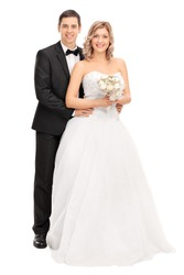 Full length portrait of a young bride and groom posing together isolated on white background