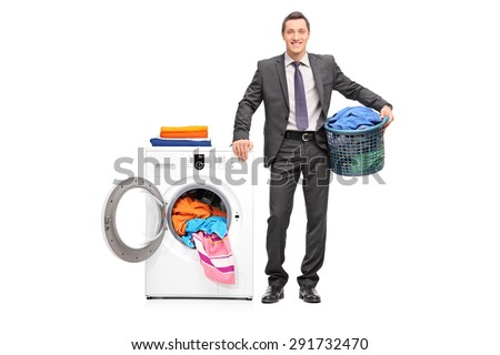 Full length portrait of a young businessman holding a laundry basket and posing next to a washing machine isolated on white background