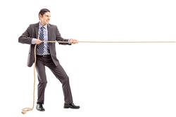 Full length portrait of a young businessman in suit pulling a rope isolated on white background