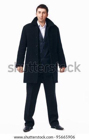 Full length portrait of a young businessman in the black coat.