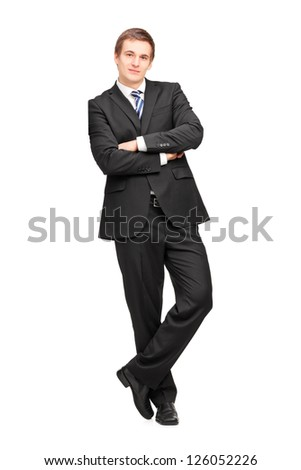 Full length portrait of a young businessman leaning against wall isolated on white background