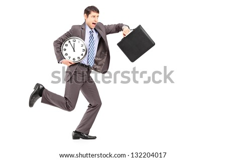Full length portrait of a young businessman running late with a clock and a briefcase isolated on white background