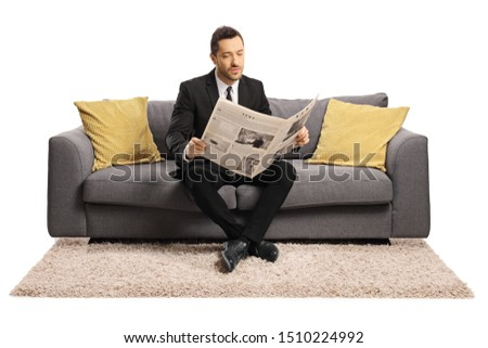 Full length portrait of a young businessman sitting on a sofa and reading a newspaper isolated on white background