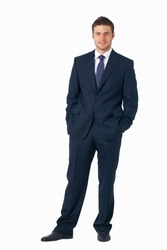 Full length portrait of a young businessman standing with his hands in the pockets.