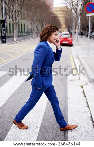 Full length portrait of a young businessman talking on his mobile phone while walking in the street, man in suit walking down a city street having phone conversation