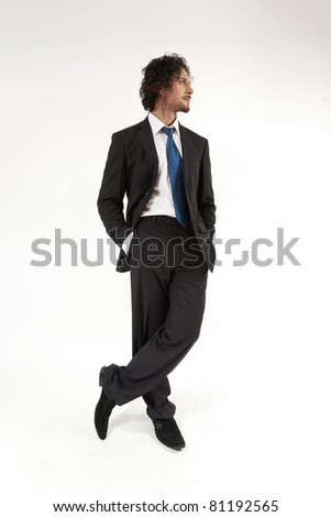 full length portrait of a young businessman wearing a suit and a neck tie.