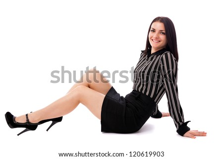 Full length portrait of a young businesswoman sitting on the floor isolated on white background