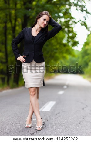 Full length portrait of a young businesswoman standing on the road with hand on hip and crossed legs