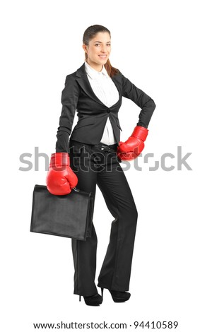 Full length portrait of a young businesswoman with boxing gloves holding a briefcase isolated on white background