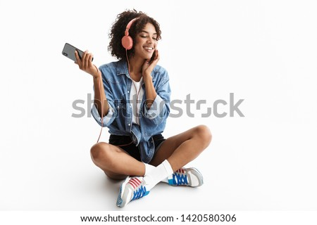 Full length portrait of a young cheerful african woman wearing casual denim clothes isolated over white background, listening to music headphones, holding mobile phone, dancing