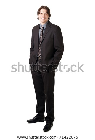 Full length portrait of a young confident businessman standing with hands in the pockets and smiling