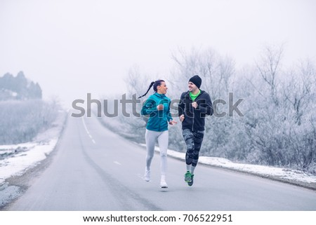 Full length portrait of a young couple running on an open road in the winter. #706522951