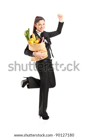 Full length portrait of a young female holding a paper bag with groceries isolated on white background