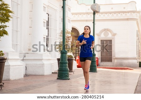 Full length portrait of a young female runner training in the city #280405214