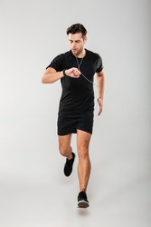 Full length portrait of a young fit sportsman in earphones listening to music while running and looking at his wristwatch isolated over gray background