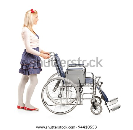Full length portrait of a young girl pushing a wheelchair isolated on white background