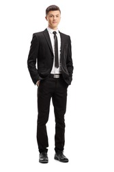 Full length portrait of a young male adult in an elegant suit posing with his hands in pocket isolated on white background