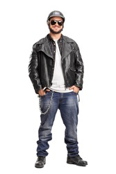 Full length portrait of a young male biker in a black leather jacket and a black helmet isolated on white background