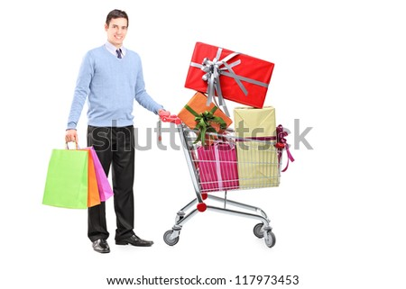 Full length portrait of a young male posing next to a shopping cart full of gifts isolated on white background