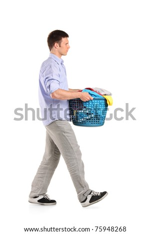 Full length portrait of a young man carrying a laundry basket isolated on white background