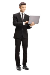 Full length portrait of a young man in a suit standing and typing on a laptop computer isolated on white background