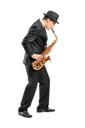 Full length portrait of a young man playing on saxophone isolated on background