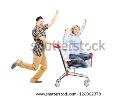 Full length portrait of a young man pushing a woman in a shopping cart isolated on white background