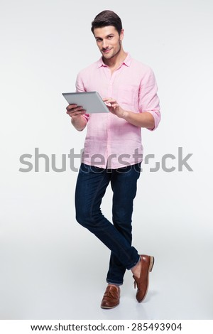 Full length portrait of a young man using tablet computer over gray background and looking at camera