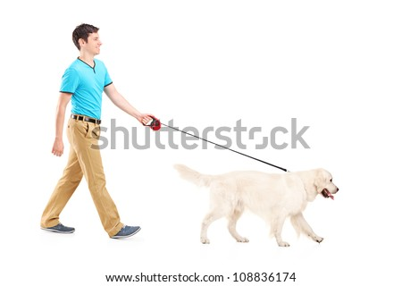 Full length portrait of a young man walking a dog, isolated on white background