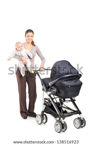 Full length portrait of a young mother with a baby and a pushchair, isolated on white background
