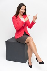 Full-length portrait of a young pretty brunette woman 30 years old in a bright red business suit with beautiful dark hair. Sits on a white background, talking, showing hands, with emotions