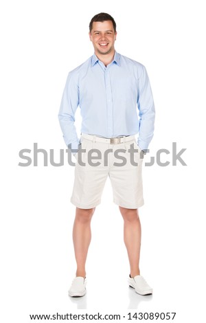 Full length portrait of a young professional adult male wearing a blue buttoned shirt and beige shorts. Image is isolated on a white background.