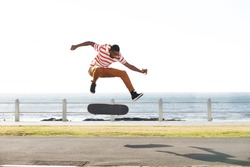 Full length portrait of a young skateboarder doing tricks and jumping on the road by the beach